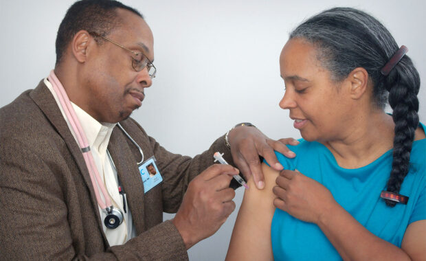 Black doctor vaccinating Black woman